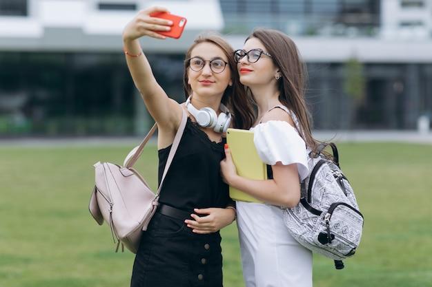 Dwie piękne beztroskie dziewczyny biorące selfie ze smartfonem. młode radosne wesoły dziewczyny przy selfie. najlepsi przyjaciele robią zdjęcia