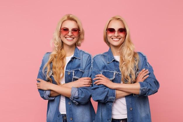 Dwie piękne białogłowe kobiety w okularach przeciwsłonecznych i dżinsach, składające ręce na piersi, stojąc na różowym tle, uśmiechając się szeroko, patrząc wesoło w kamerę
