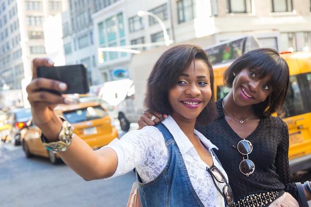 Dwie piękne czarne kobiety biorąc selfie w nowym jorku