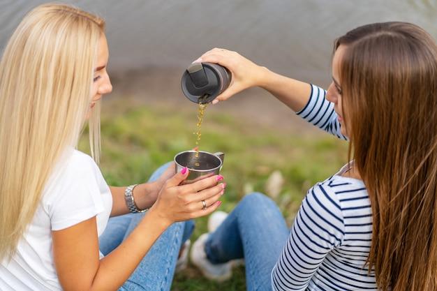 Dwie piękne dziewczyny cieszą się przyrodą i piją gorącą herbatę na brzegu jeziora z pięknym widokiem