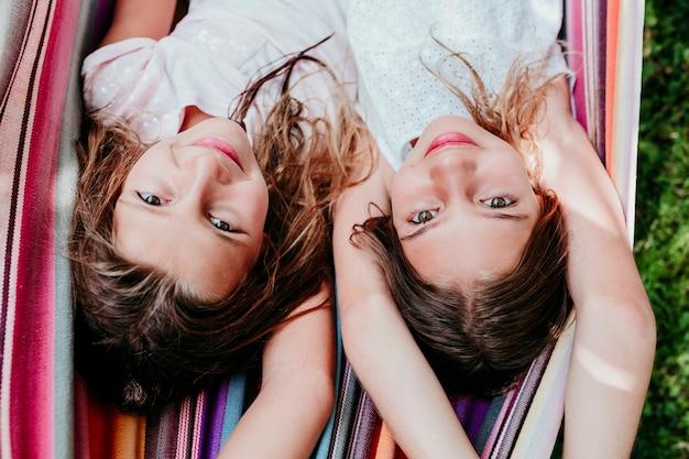 Dwie piękne dziewczyny nastolatki leżące na hamaku kolorowe w ogrodzie. patrząc w kamerę. styl życia, relaks i zabawa na świeżym powietrzu