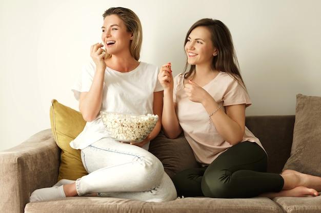 Dwie piękne dziewczyny oglądają program telewizyjny i jedzą popcorn w domu