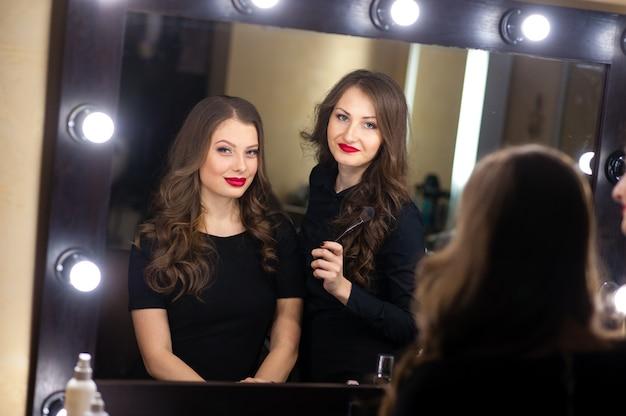 Dwie piękne dziewczyny patrzą w lustro