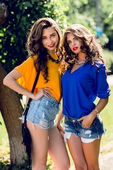Dwie piękne dziewczyny pozują w parku