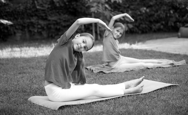 Dwie piękne dziewczyny rozciągające się i ćwiczące jogę na trawie