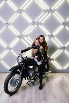 Dwie piękne dziewczyny ubrane w kostiumy zawodników i siedzące na motocyklu w studio