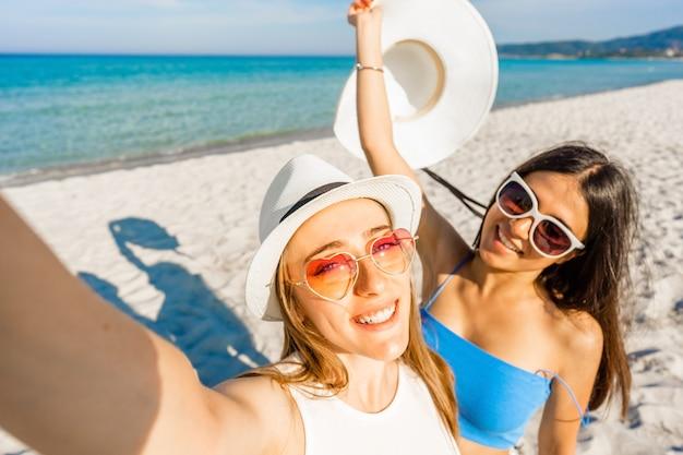 Dwie piękne dziewczyny w białych kapeluszach, biorąc autoportret, ciesząc się letnimi wakacjami na tropikalnej plaży. pov młodej blondynki używającej smartfona do sfotografowania się z najlepszą nastoletnią przyjaciółką