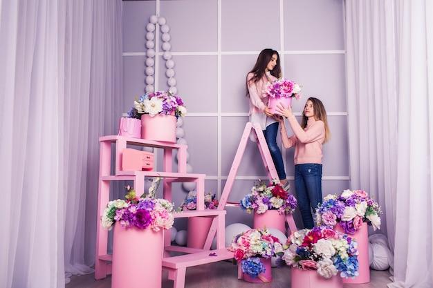 Dwie piękne dziewczyny w dżinsach i różowej kurtce na tle dekoracji kwiatowych w studio.