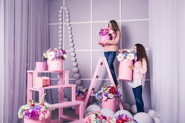 Dwie piękne dziewczyny w dżinsach i różowym swetrze w studio z wystrojem kwiatów w koszach.