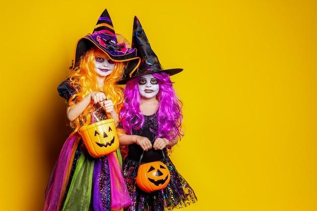 Dwie piękne dziewczyny w strojach czarownicy i kapeluszach na żółtym tle straszą i robią miny.