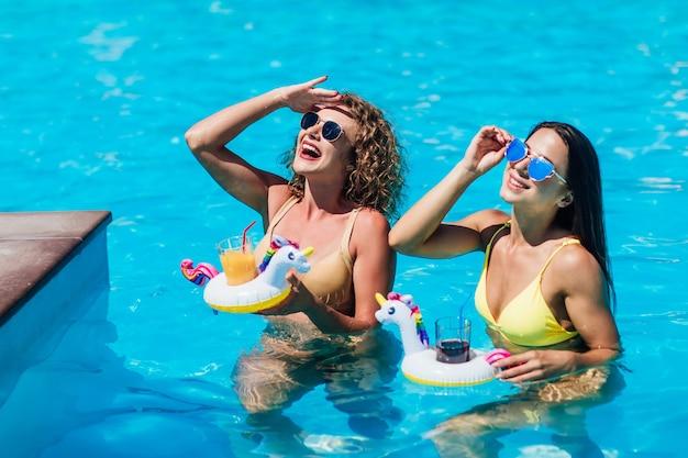 Dwie piękne dziewczyny w strojach kąpielowych na basenie?