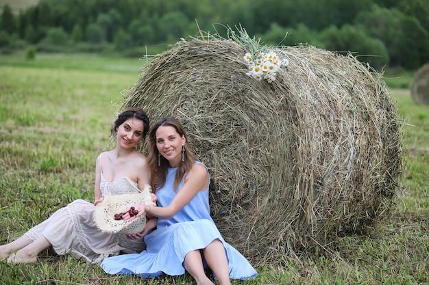 Dwie piękne dziewczyny w sukienkach w letnim polu z jagodami