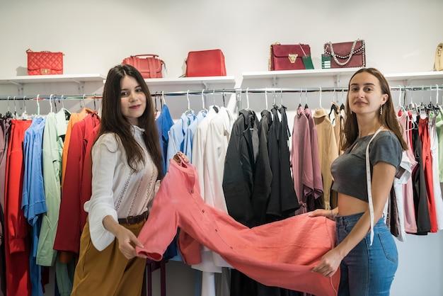 Dwie piękne dziewczyny wybierają nowe ubrania w sklepie z modą na uroczystość. styl życia