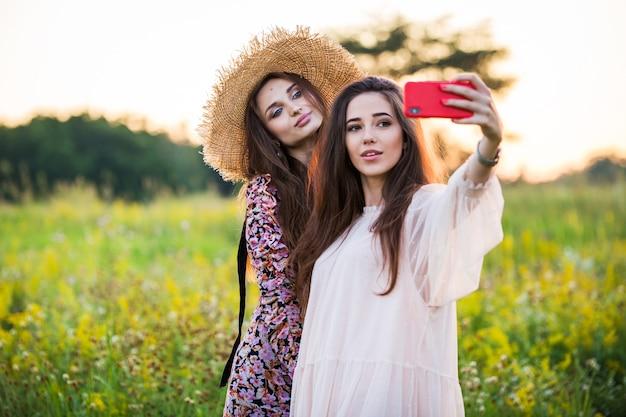 Dwie piękne dziewczyny z europy robią sobie selfie na świeżym powietrzu