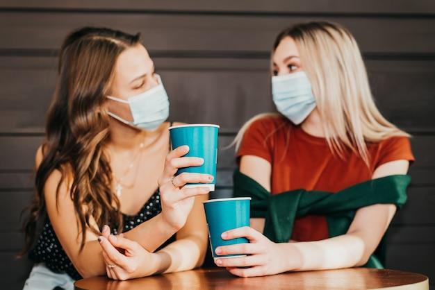 Dwie piękne dziewczyny z maskami na twarzach spędzają razem czas przy kawie i pijąc herbatę