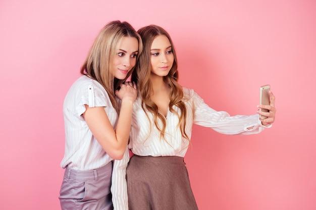 Dwie piękne i uśmiechnięte dziewczyny (mama i córka) robią sobie zdjęcia selfie telefonem na różowym tle w studio. pojęcie egoizmu i miłości własnej