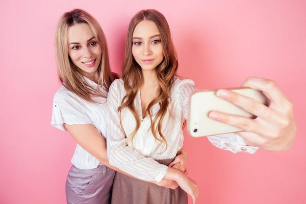 Dwie piękne i uśmiechnięte osoby płci żeńskiej matka i córka robią sobie zdjęcia selfie telefonem na różowym tle w studio. pojęcie miłości i rodziny.