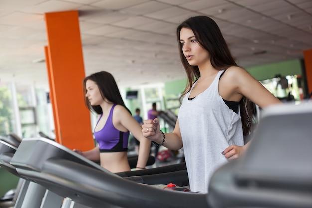 Dwie piękne kobiety, bieganie na bieżni w siłowni. ładne dziewczyny na bieżni w pomieszczeniu trenują i uśmiechają się