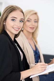 Dwie piękne kobiety biznesu siedzi na seminarium i pisze coś. edukacja biznesowa i koncepcja sukcesu