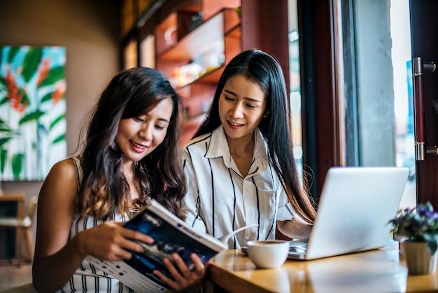 Dwie piękne kobiety mówią wszystko razem w kawiarni kawiarni