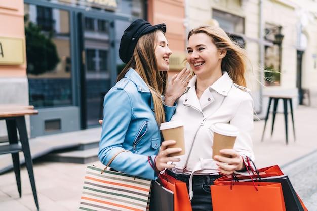 Dwie piękne kobiety na środku ulicy z kawą i torbami na zakupy w rękach stoją i dyskutują z zainteresowaniem
