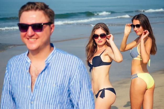 Dwie piękne kobiety patrzą zakochanymi oczami na samotnego mężczyznę spacerującego po plaży