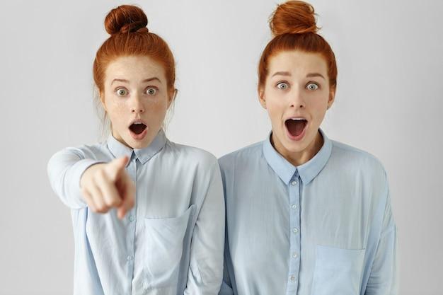 Dwie piękne kobiety rasy białej, wyglądające podobnie, z kokami do włosów, ubrane w te same formalne koszule