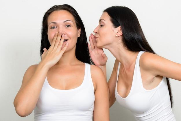 Dwie piękne kobiety razem na białej ścianie