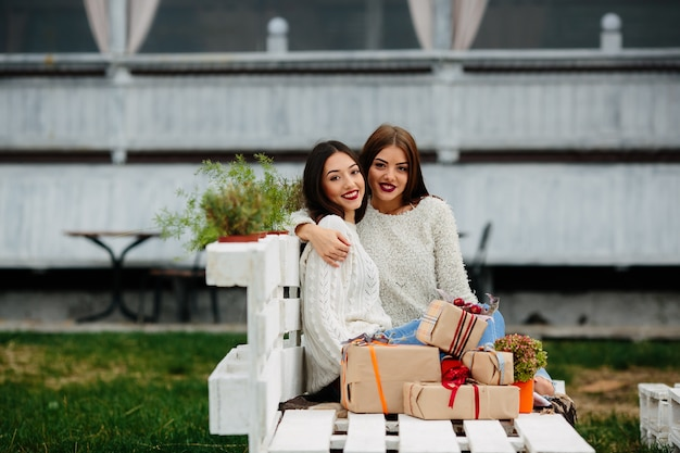 Dwie piękne kobiety siedzą na ławce, trzymając prezenty w rękach i patrząc