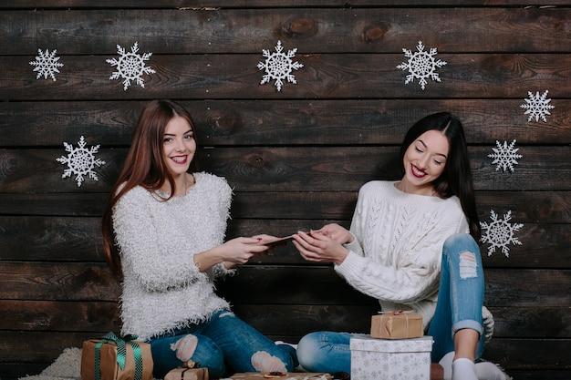 Dwie piękne kobiety siedzą na podłodze z tabletem, między prezentami na boże narodzenie