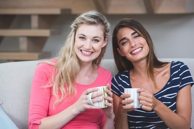 Dwie piękne kobiety siedzące obok siebie z kubkiem kawy