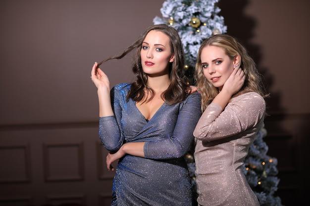 Dwie piękne kobiety świętują boże narodzenie wraz z modną sukienką. boże narodzenie w domu