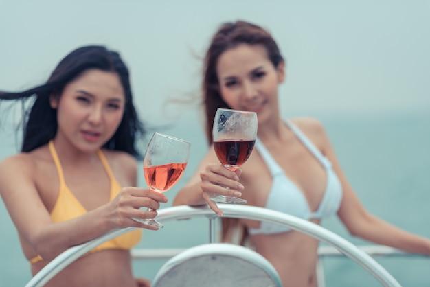 Dwie piękne kobiety w bikini popijają wino na jachcie.