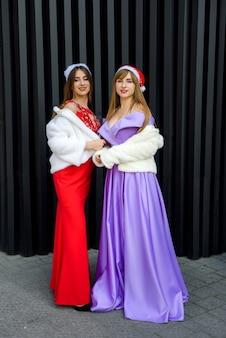 Dwie piękne kobiety w eleganckich sukienkach świętują nowy rok