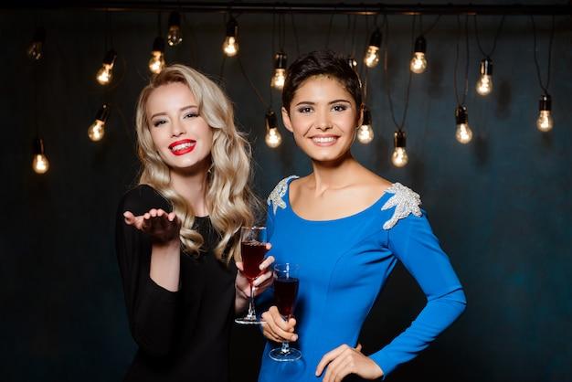 Dwie piękne kobiety w strojach wieczorowych, uśmiechając się, trzymając kieliszki do wina