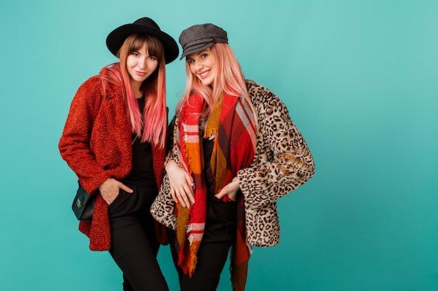 Dwie piękne kobiety w stylowych płaszczach ze sztucznego futra i wełnianym szaliku pozują na turkusowej ścianie