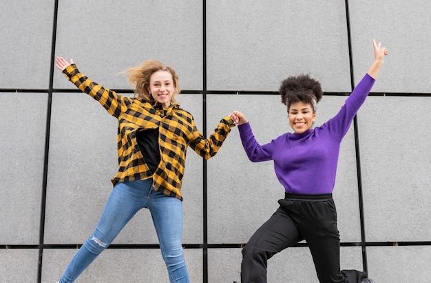 Dwie piękne kobiety z afryki i rasy kaukaskiej, skaczące po mieście