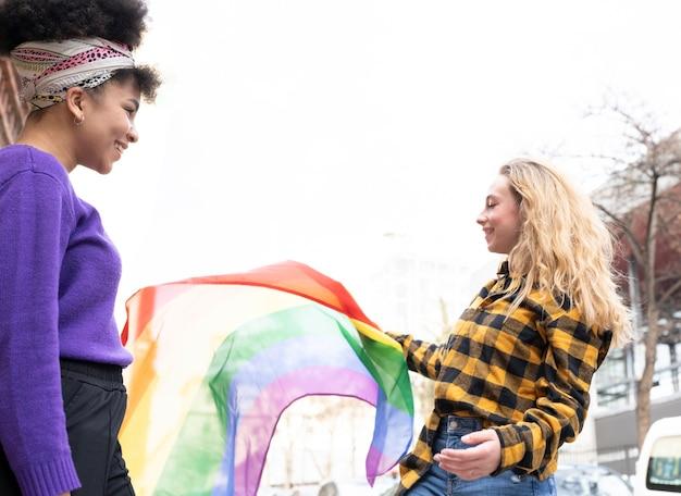 Dwie piękne kobiety z afryki i rasy kaukaskiej, z flagą dumy gejowskiej