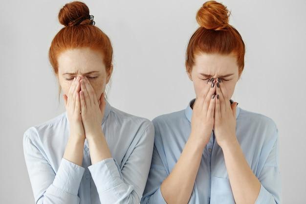 Dwie piękne koleżanki lub siostry wyglądające podobnie, zakrywające twarze rękami