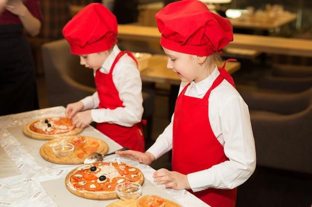 Dwie piękne kucharki w białych koszulach i czerwonych fartuchach w restauracji robią pizzę