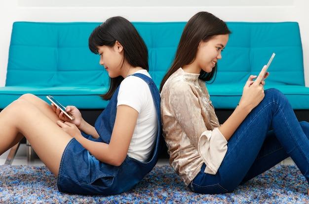 Dwie piękne młode azjatki leżą na plecach i korzystają z urządzeń mobilnych, smartfonów i tabletów podłączonych do internetu