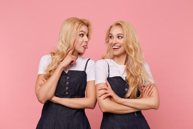 Dwie piękne młode białogłowe kobiety ubrane w dżinsowe sukienki i białe t-shirty są w miłym nastroju i bawią się razem, pozując na różowym tle
