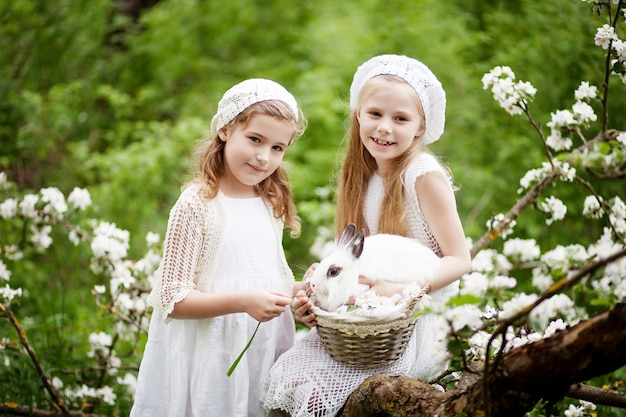 Dwie piękne młode dziewczyny bawiące się z białym królikiem w ogrodzie kwitnącej wiosny. wiosenna zabawa dla dzieci. czas wielkanocy