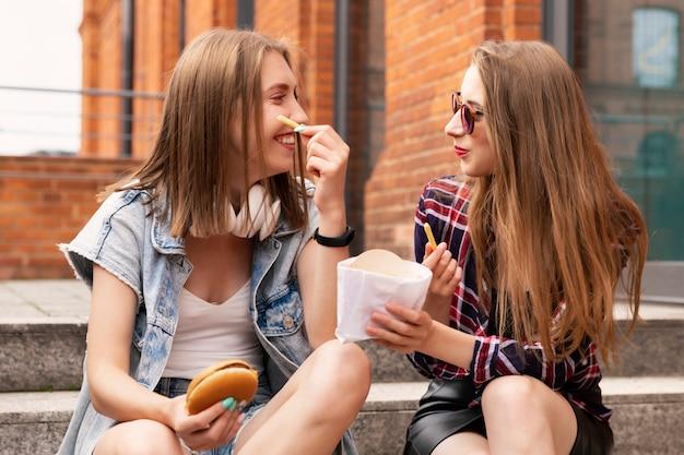 Dwie piękne młode dziewczyny jedzą fast food na ulicy.