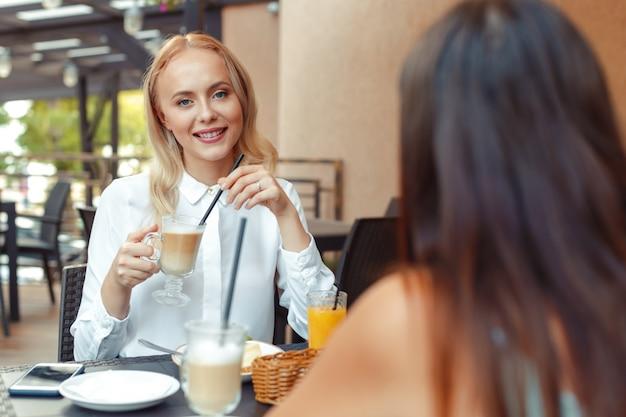 Dwie piękne młode dziewczyny siedzą przy stoliku w kawiarni