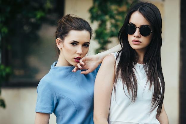 Dwie piękne młode dziewczyny w sukienkach pozują przed domem