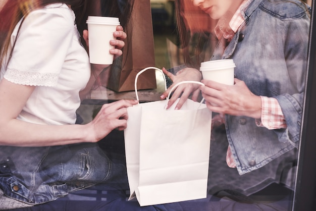 Dwie piękne młode kobiety siedzą w kawiarni, piją kawę i prowadzą przyjemną rozmowę po zakupach.