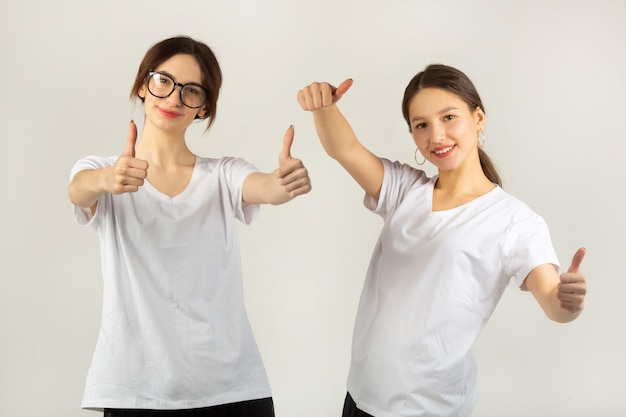 Dwie piękne młode kobiety w białych koszulkach na białym tle z gestem ręki
