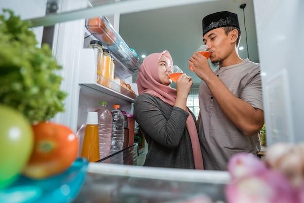 Dwie piękne pary muzułmańskie rozbijające szybki iftar przed otwartą lodówką w kuchni