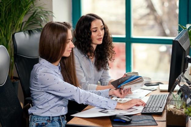 Dwie piękne projektantki lub architekci wspólnie rozwiązują zadania podczas pracy w nowoczesnym biurze przy oknie. kreatywni ludzie lub koncepcja biznesowa reklamy.